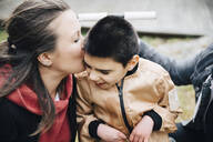 Mother kissing disabled son sitting on wheelchair in yard - MASF13875