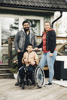 Portrait of smiling parents standing by disabled son sitting on wheelchair against house - MASF13878