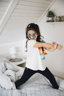 Portrait of happy girl wearing sunglasses dancing on bed at home - MASF13881