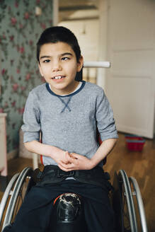 Portrait of autistic boy sitting on wheelchair at home - MASF13890