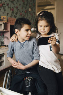Sister showing video to autistic brother on mobile phone at home - MASF13896