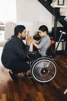 Side view of father holding autistic son's hands sitting on wheelchair at home - MASF13899