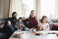 Portrait of smiling family sitting on sofa against window at home - MASF13911