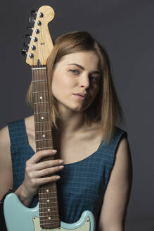 Portrait confident, beautiful young woman with electric guitar - FSIF04328