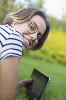 Portrait smiling young woman with digital tablet and headphones in grass - FSIF04331