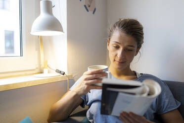 Young woman reading book on couch at home - GUSF02491