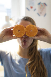 Playful young woman covering her eyes with oranges at home - GUSF02500