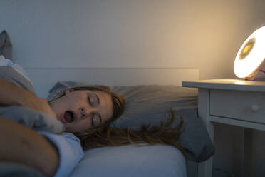 Young woman lying in bed at home at night yawning - GUSF02512