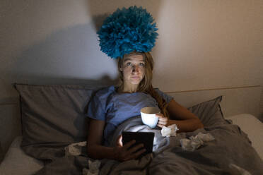 Ill young woman lying in bed at home with cup of tea at night using tablet - GUSF02518