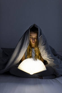 Young woman reading illuminated book in bed at home - GUSF02524