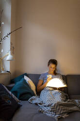 Young woman reading illuminated book on couch at home - GUSF02530
