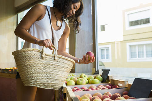 Young woman in organic store choosing apples - JPTF00285