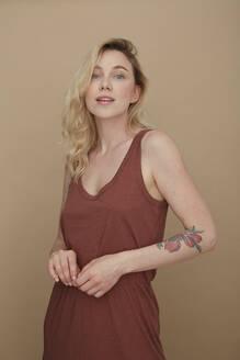 Portrait of blond tattooed woman wearing summer fashion - PGCF00007