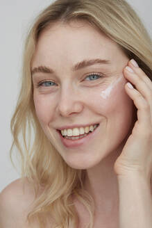 Portrait of smiling young woman applying cream on her face - PGCF00022