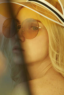 Portrait of young blond woman wearing sunglasses in summer - PGCF00025