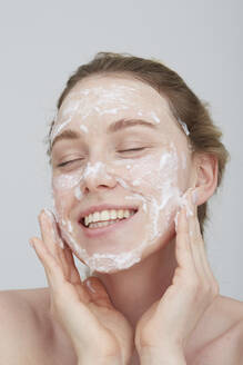 Portrait of blond young woman with eyes closed applying cream on her face - PGCF00028