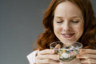 Portrait of smiling redheaded woman smelling blossoms in glass bowl - KNSF06501