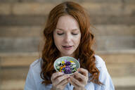Portrait of redheaded woman looking at blossoms in a bowl - KNSF06513