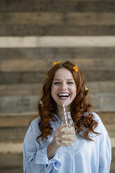 Portrait of laughing redheaded woman with blossoms in hair drinking lemonade - KNSF06516