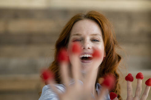 Portrait of laughing redheaded woman with raspberries on her fingertips - KNSF06525