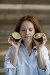 Portrait of redheaded woman with eyes closed holding sliced avocado - KNSF06528