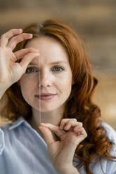 Portrait of redheaded woman holding thread of dental floss - KNSF06531
