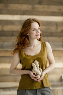 Portrait of redheaded woman with ginger root - KNSF06534