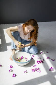 Redheaded woman sitting on the floor with bowl of orchid blossom and natural sponge - KNSF06546