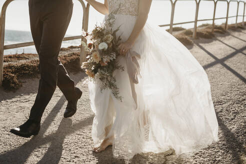 Close-up of bride and groom walking on path at the coast - LHPF00794