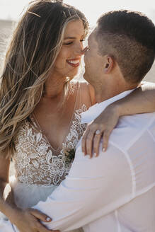 Happy affectionate bride and groom hugging outdoors - LHPF00797