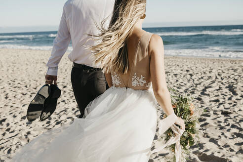 Rear view of bride and groom walking on the beach - LHPF00809