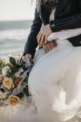 Close-up of affectionate bride and groom on the beach - LHPF00818