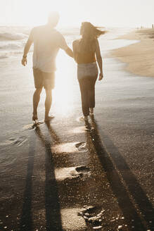 Affectionate young couple walking at the seashore at sunset - LHPF00836