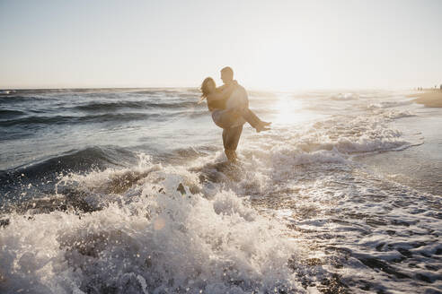 Happy young man carrying girlfriend at the seashore at sunset - LHPF00839