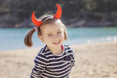Portrait of girl on the beach wearing devil's horns - XCF00202