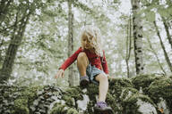 Blond girl sitting on rock in the forest - DWF00494