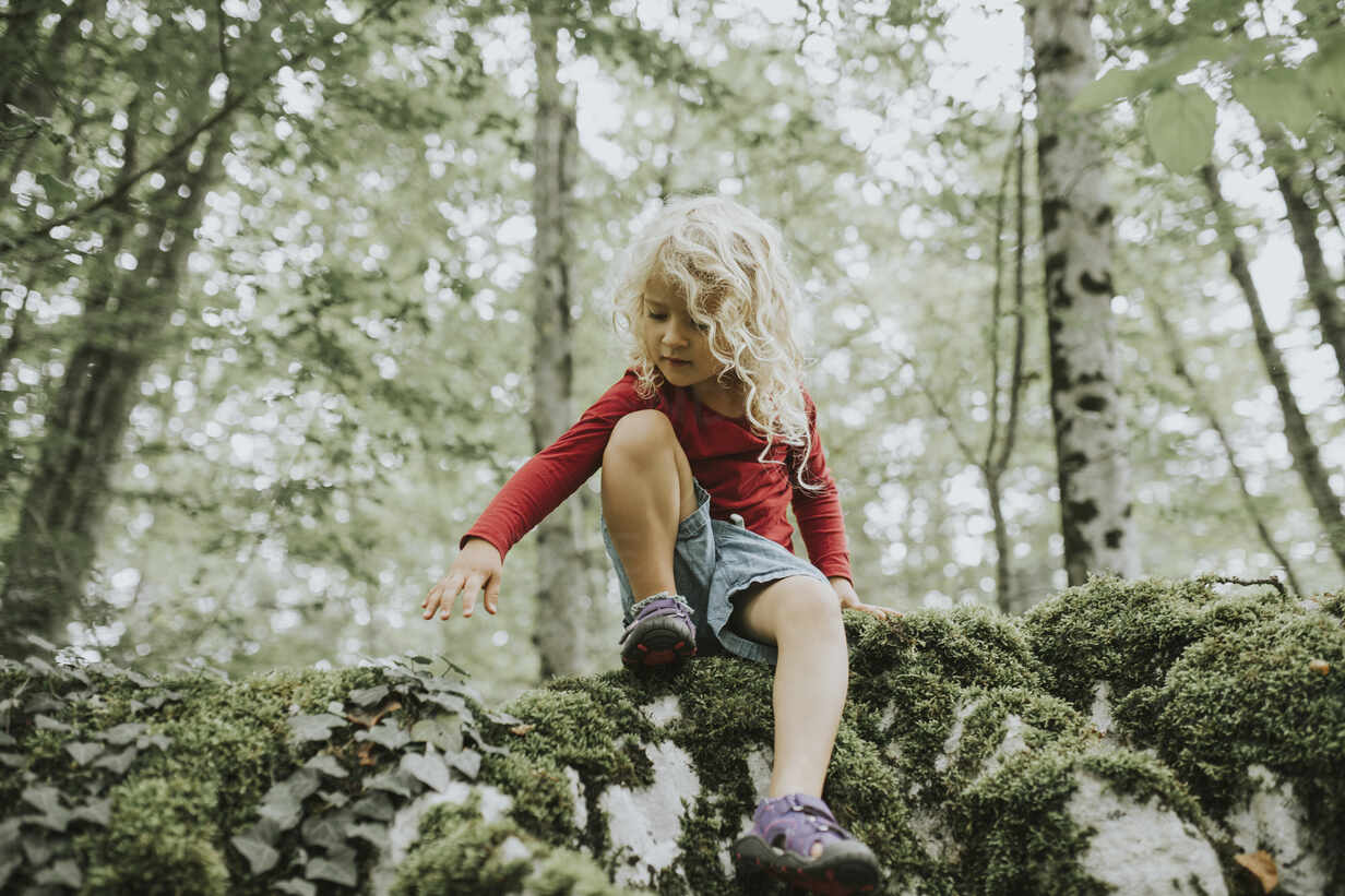 Blond girl sitting on rock in the forest - DWF00494 - Frederik Franz/Westend61