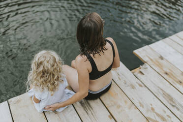 Mother and daughter sitting on jetty at a lake - DWF00500