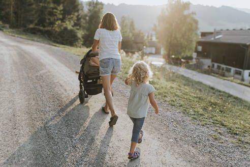 Mother with daughter, stroller and dog walking on forest path - DWF00506