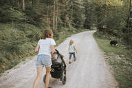 Mother with daughter, stroller and dog walking on forest path - DWF00509