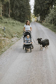 Mother with baby in stroller and dog walking on forest path - DWF00512