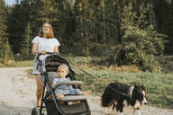 Mother with baby in stroller and dog walking on forest path - DWF00515