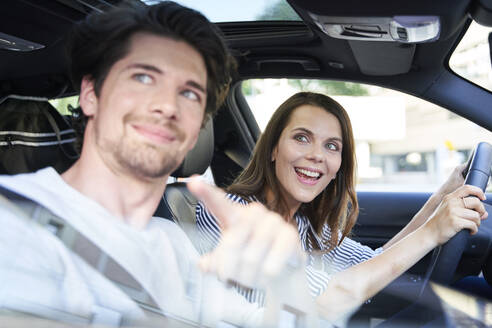 Happy couple in a car with woman driving and man pointing his finger - PNEF01977