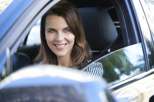 Portrait of smiling woman driving car - PNEF01983