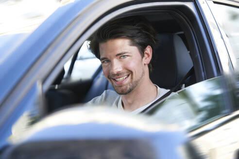 Portrait of smiling man driving car - PNEF01986