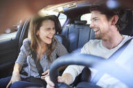 Laughing couple in a car with man driving - PNEF01989