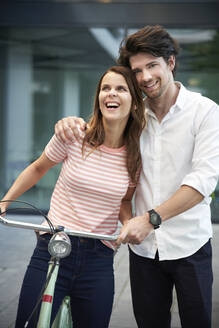 Happy couple with bicycle in the city - PNEF02046