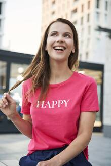 Portrait of laughing woman wearing pink t-shirt in the city - PNEF02070