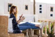 Smiling redheaded young woman relaxing with cup of coffee on roof terrace looking at cell phone - AFVF03952