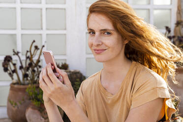 Portrait of smiling redheaded young woman with smartphone on terrace - AFVF03955